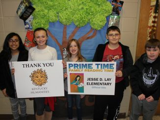 Students pose with posters announcing that Prime Time Reading is coming to Lay Elementary