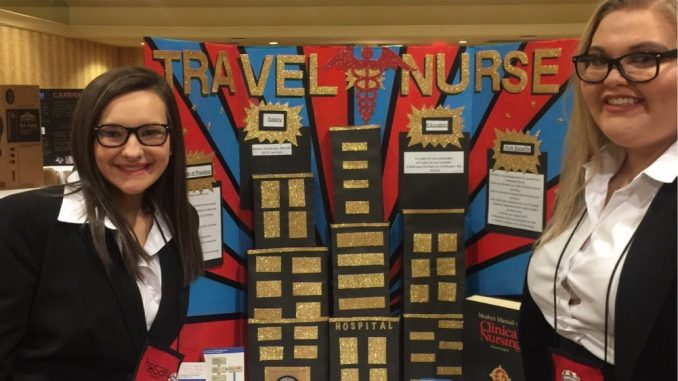 Knox HOSA members pose in front of their display showing information about travel nurses.