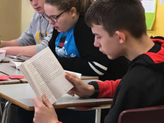 """A close up of students reading the book """"All of the Above""""."""