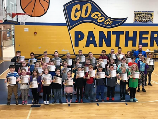Students hold awards received during Central Elementary's Panther Way assembly on Friday, February 8.