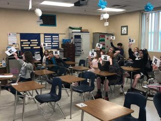 Students hold up papers, no technology needed, to use Plicker technology to report their response.