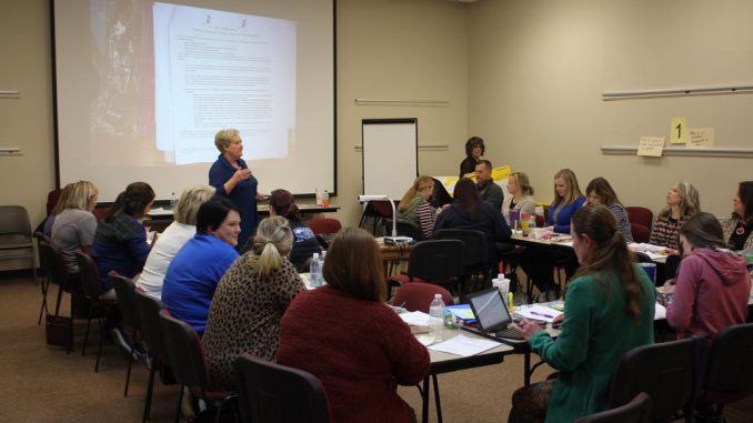 Teachers are shown engaged in learning about On Demand writing by presenters Abell and Atherton.