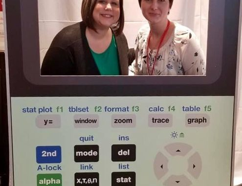 Fatemia Fuson and Rachel Wyatt pose for a photo in a calculator cut-out while at the T3 conference.