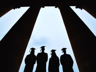 Photo of four graduates shown in dark figure with clouds behind them and columns to each side.