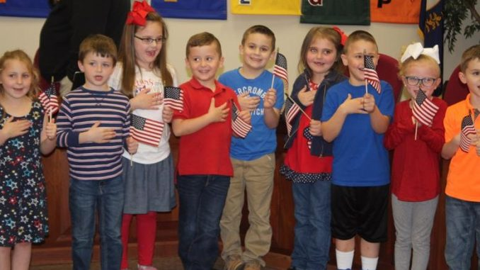 Students are shown leading the Pledge of Allegiance at the March 2019 board meeting.