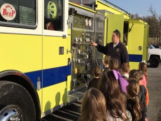 Students are shown lined up to see inside a fire truck at Lynn Camp Elementary.