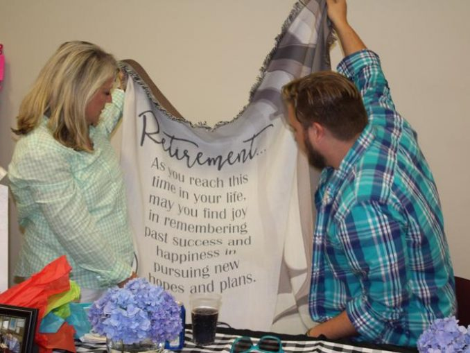 Charlotte and her son Tyler hold up a retirement gift during a luncheon at the Annex.