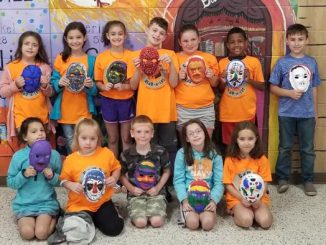 Students hold masks created during Camp Read a Lot.