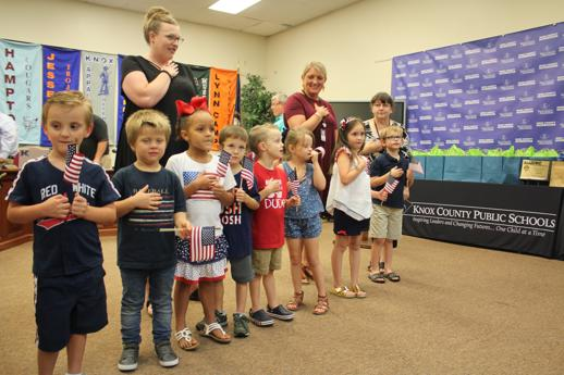 Central Elementary students line up in front of the Board and audience to recite the Pledge. They are holding miniature American flags.