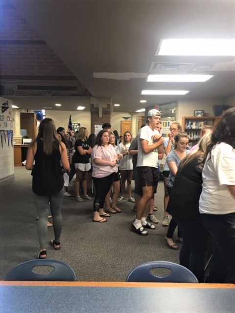 Link Crew leaders are shown in the library planning a group activity together.