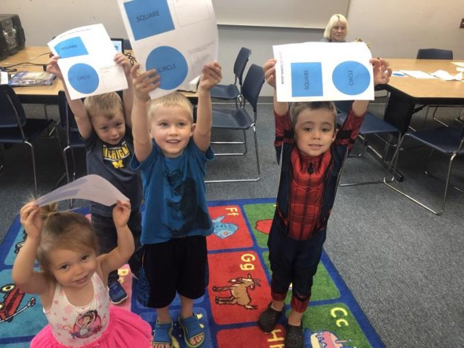 Kids shown at Learn and Play groups hosted by Save the Children. Students are holding up shapes on paper.
