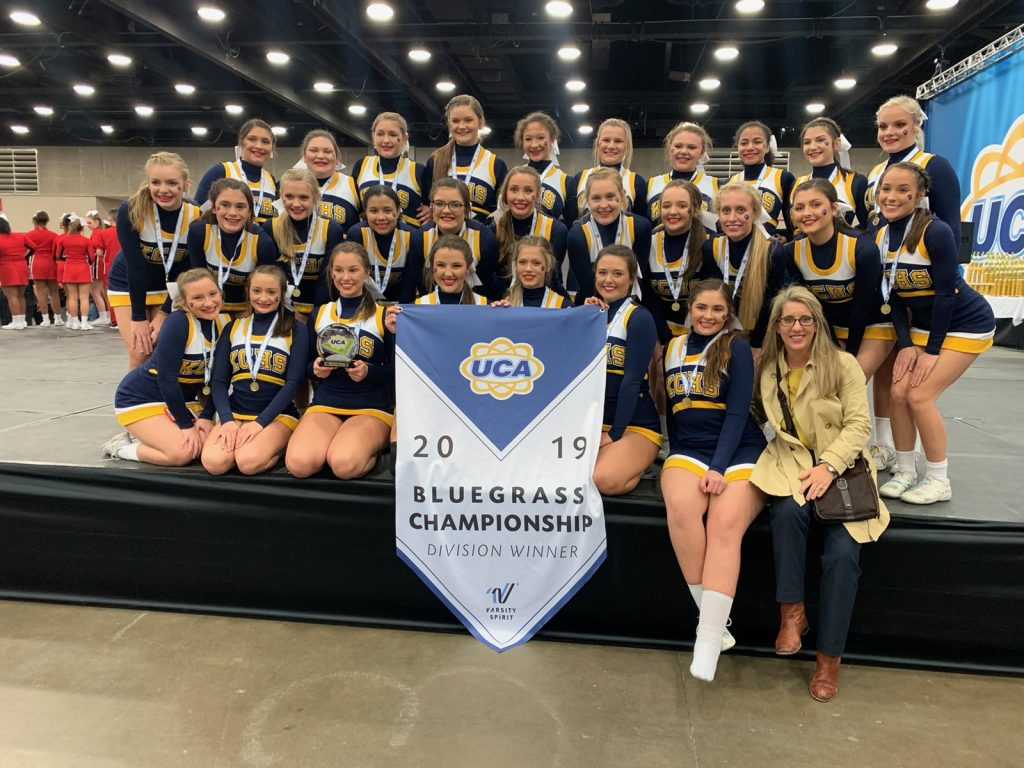 Knox Central cheerleaders shown on stage with an award winning banner from the UCA Bluegrass cheer competition.