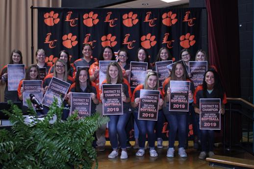Softball players at Lynn Camp pose in front of the LC backdrop during the November Board meeting.