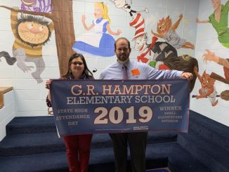 Gina Sears and Brian Frederick hold the G.R. High Attendance Banner
