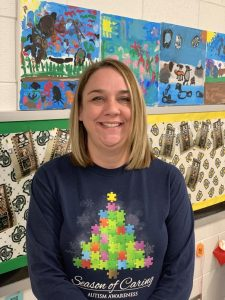 Mrs. Holstein poses for a quick photo in front of a bulletin board inside her classroom.