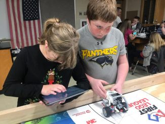 One student uses an iPad to control the robot while another sets it into motion.