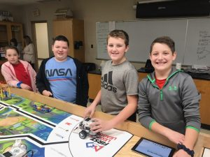 With smiles on their faces, these robot engineers paused testing their robot for a photo.