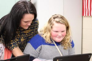 Mrs. Frederick is shown helping a student with a computer problem on a Chromebook.