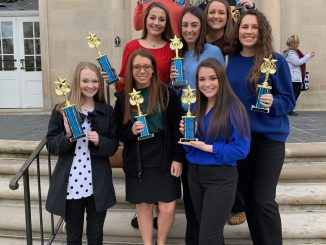 DECA students are shown outside a building at EKU holding their trophies from the regional competition.