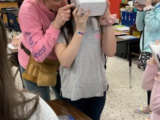 Mrs. Davis is shown adjusting the VR headset for a student.