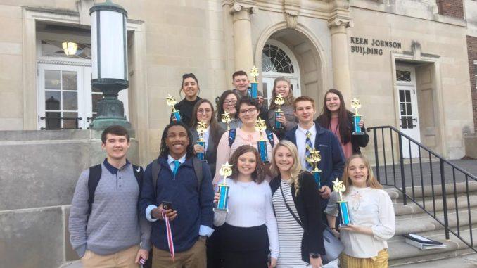 Students hold winning trophies outside of EKU.