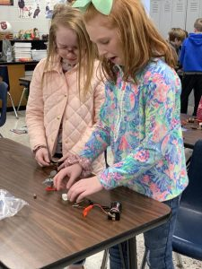 Two female students test circuits using batteries.
