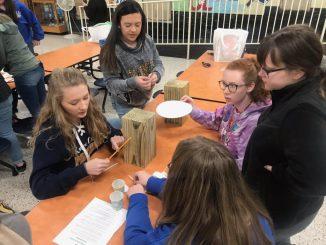 Five students use random materials to solve a problem.