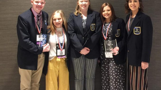 Five Lynn Camp students shown with medals after winning at DECA state competition.