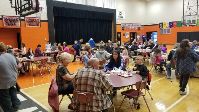 Students are shown having a gravy breakfast with their grandparents in the gymnasium at Lynn Camp Elementary School