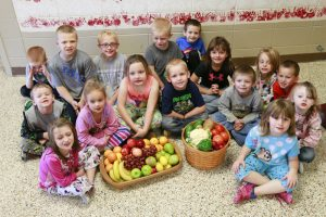 Students pose with baskets full of fruits and vegetables that are made possible by a federal FFVP grant