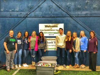 Students are shown with Bluegrass Care Navigators accepting totes of food.