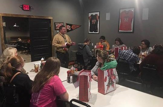 Principal Anthony Pennington and central office director Amy Pennington are shown with students leading a book study on Laws of Leadership.