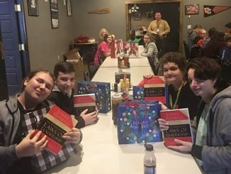 Students seated at a table show off their new book study, Laws of Leadership.