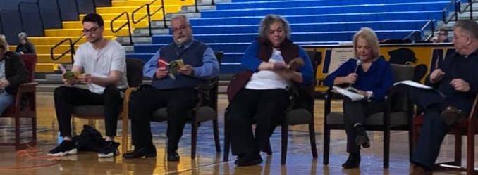 "Guest speakers are shown sitting inside KCMS gym reading from ""All of the Above"" by Shelley Pearsall."