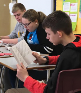 "A close up of students reading the book ""All of the Above""."
