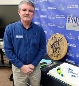 Mr. Merida is shown with gifts and a cake during his retirement luncheon.