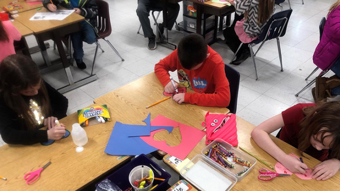 Students carefully cut out Valentine's Day hearts to send to children at St. Jude's.