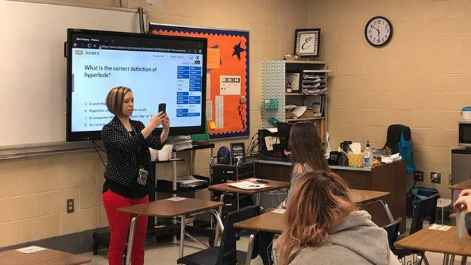 Ameila Evans is shown capturing student responses using her phone.