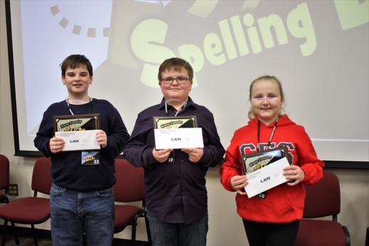 Top three winners in the Knox County Spelling Bee pose for a photo with awards and gifts from sponsors.