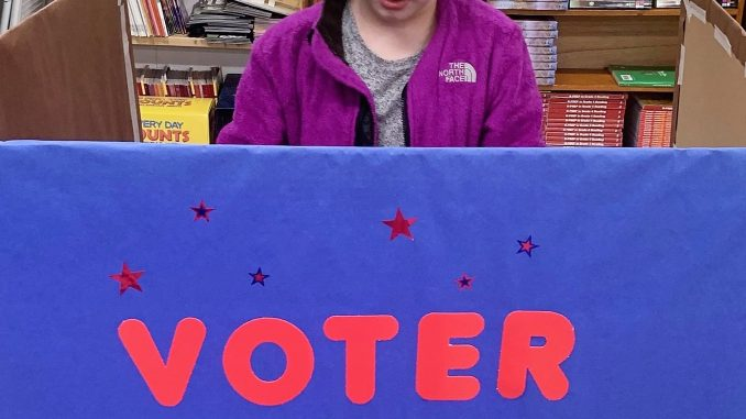 Voter in session booth at Lay Elementary 4th grade election. A student is shown casting their vote.