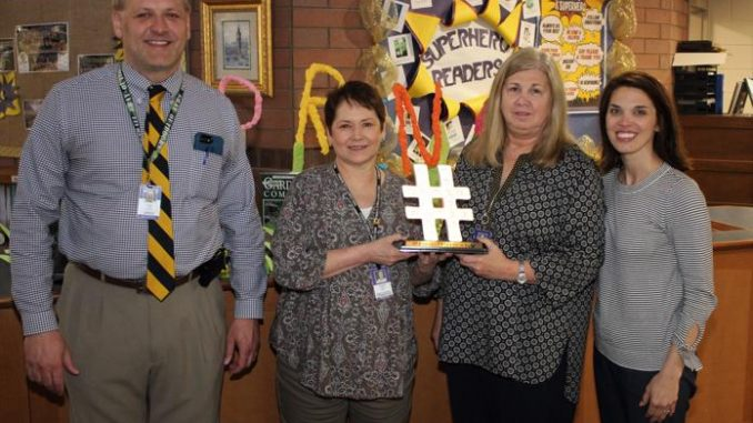 Jeff Frost (principal) and Wendy King (KEDC) are shown with Teresa Gambrel and Sherry Faulkner, recipients of the traveling #readknoxky hashtag.