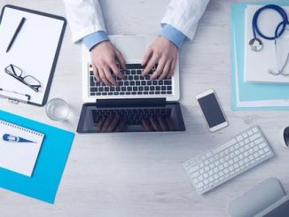 Stock image of a doctor shown with glasses, laptop, and notes.
