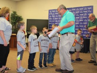Board members Kevin Hinkle and Dr. Tom Ashburn are shown presenting certificates to Dewitt kindergarten students