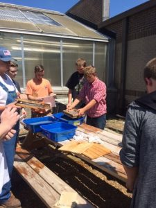 Students are shown with water pans and wood frames holding together materials to make the paper.