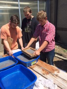 A close up of three students observing the process of using water to make paper.
