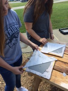 Two students unveiling two sheets of paper.