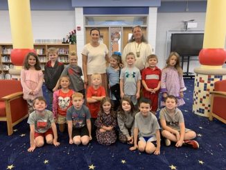 The first grade class at Central Elementary posed for a photo with Jim Redbird as they learned about Native Americans.