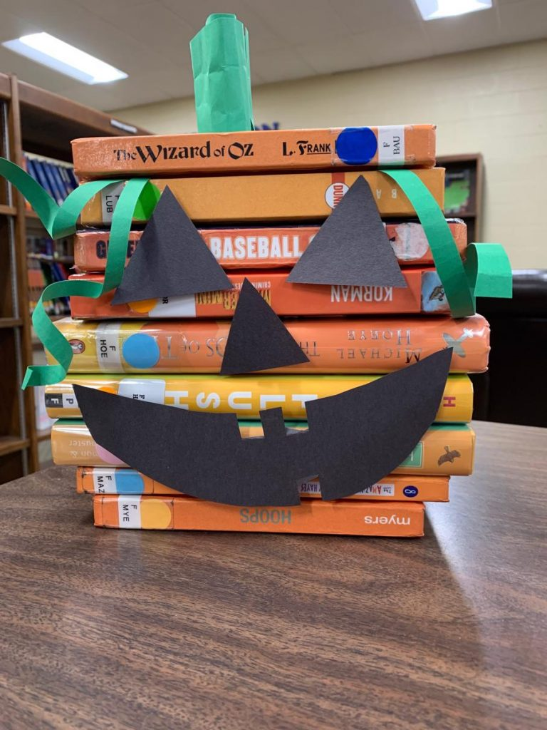 Books stacked in the library with jackolantern cut outs attached to the spines.