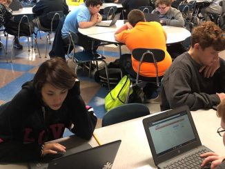 Two students are shown close up working on the timed CERT assessment using a computer.