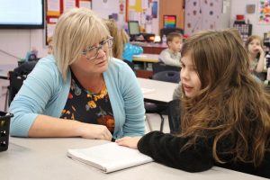 Sheila Mills is shown discussing a writing assignment with a student.